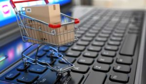 A minature shopping cart filled with shopping boxes and packages placed gently on top of a laptop keypad.